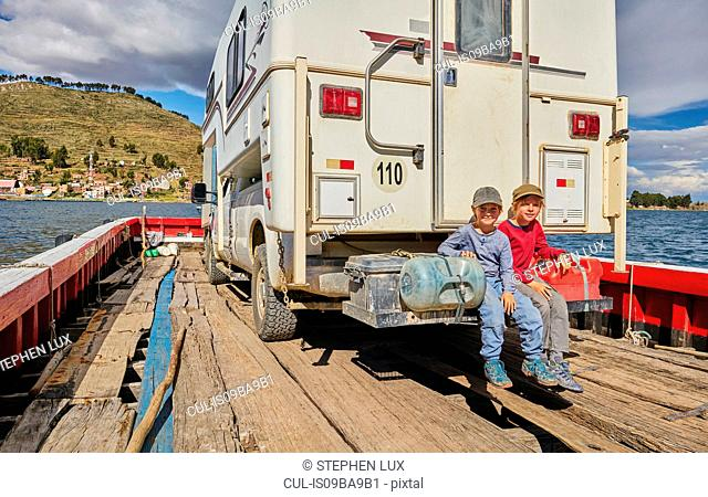 Portrait of two boys sitting at rear of recreational vehicle, on ferry, Tiquina, La Paz, Bolivia, South America