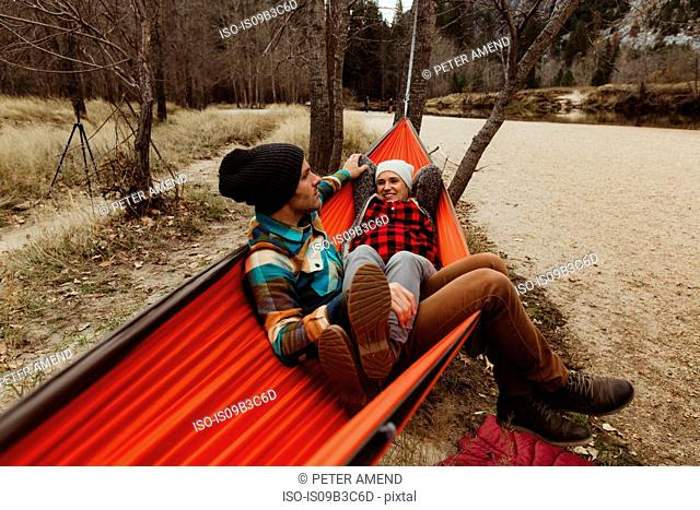 Couple reclining in red hammock at Yosemite National Park, California, USA