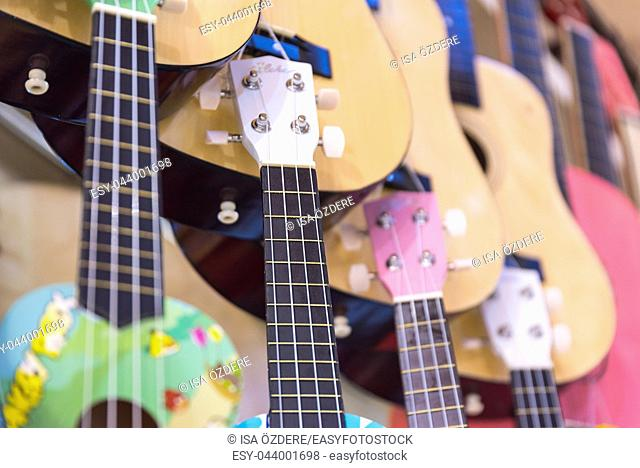 Many classic colorful wooden guitars hanging on wall of store showroom, background pattern in Istanbul grand bazaar