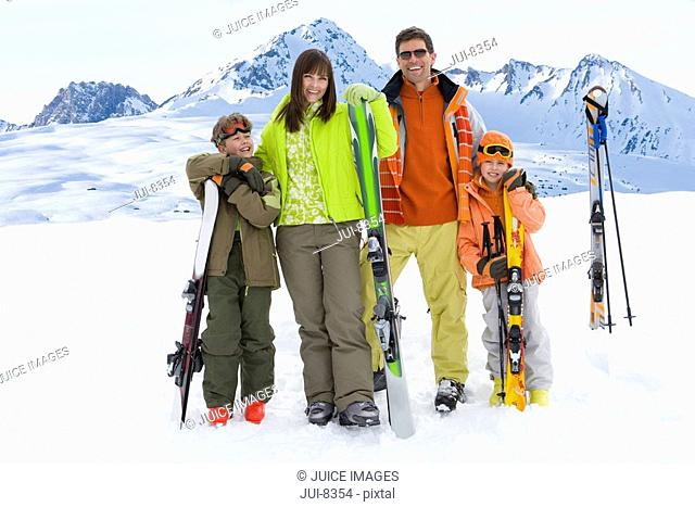 Couple with daughter and son 6-8 standing in snow with skis, smiling, portrait