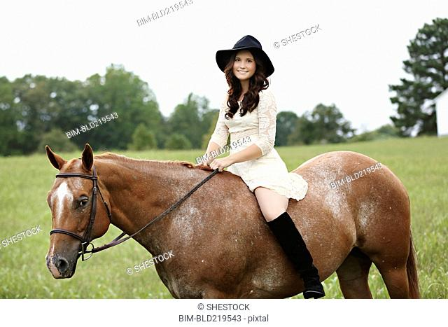 Woman riding horse in rural field