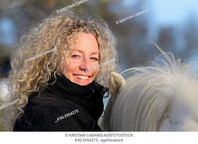 Young blond woman with Icelandic horse, Smiling and looking at the camera, Attenbach, Siegerland, North-Rhein-Westphalia, Germany, Europe