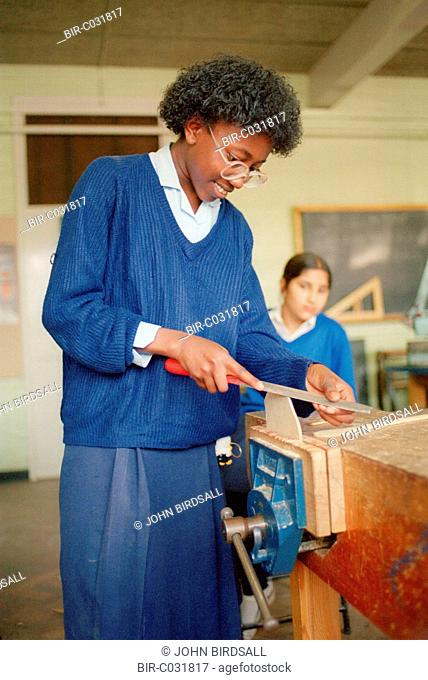 Secondary school girl using file to shape wood held in vice during Design and Technology class