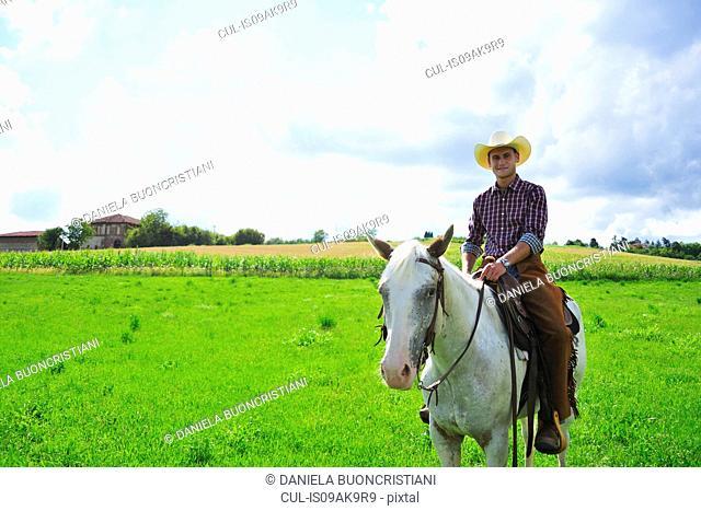 Portrait of young man in cowboy gear on horseback in field