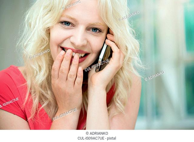 Young woman on cellphone, giggling