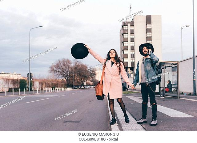 Young couple outdoors, holding hands, young woman holding hat in hand, hailing taxi