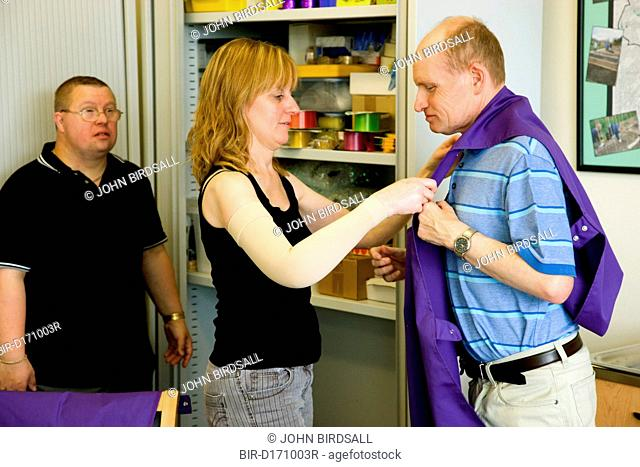 Day Service Officer helping a service user put on an apron to protect clothes during an arts and crafts activity