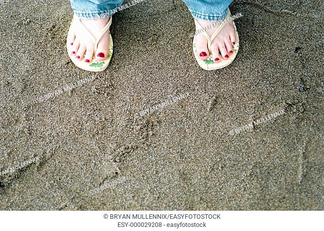 Painted toes of woman wearing thongs on beach