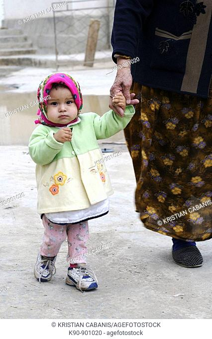 Little girl walking with her grandmother hand in hand, Ichon-Qala (Old Town), Khiva, Uzbekistan, Central Asia