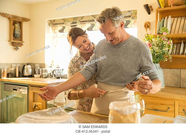 Playful mature couple baking, putting on apron in kitchen