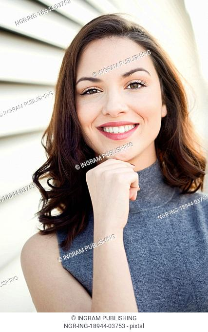 Beautiful young woman, model of fashion, smiling in urban background