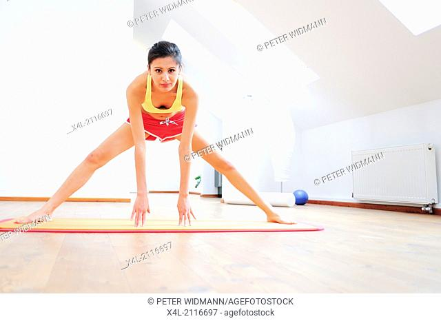 young, pretty, sportive woman, stretching (model-released)