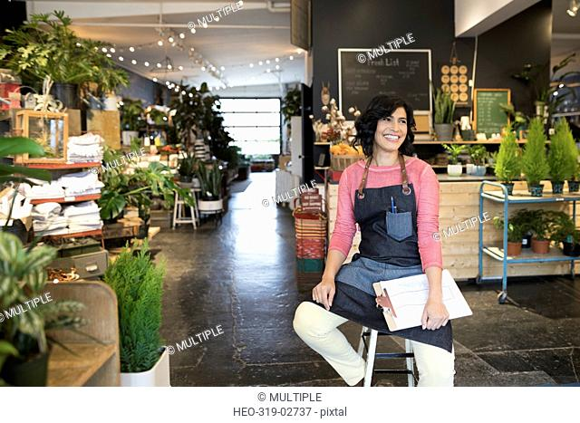 Smiling female shop owner with clipboard in plant shop