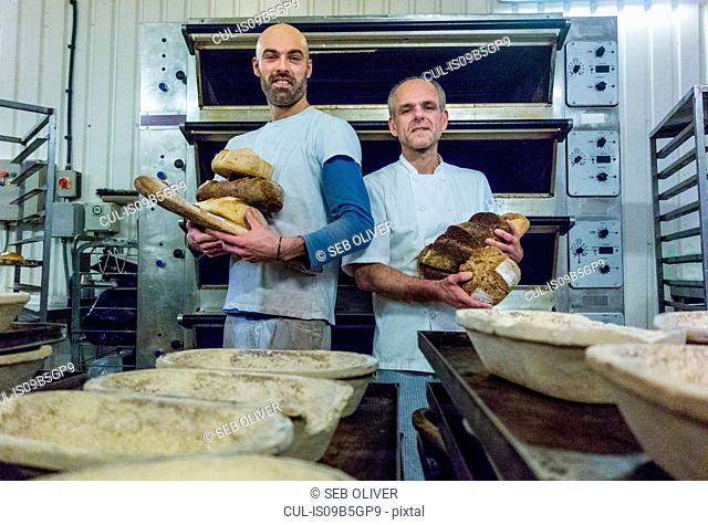Bakers holding freshly-made bread
