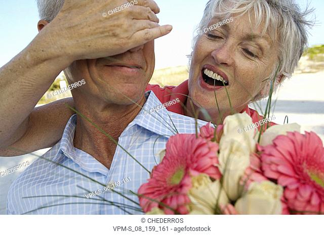 Close-up of a senior woman covering the eyes of a senior man