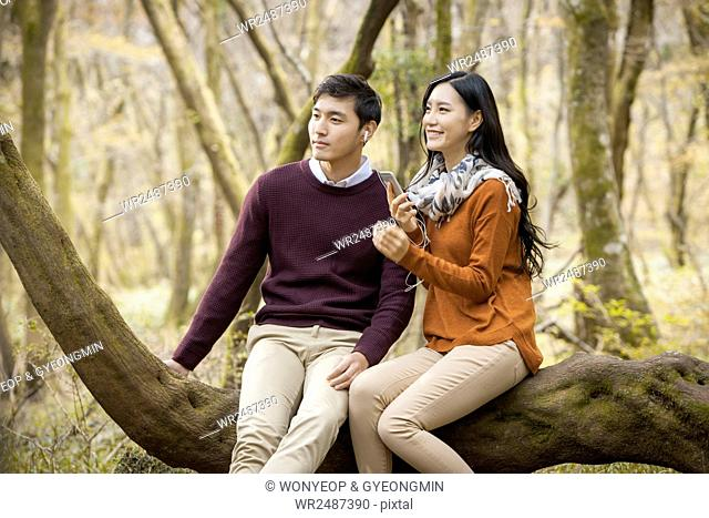 Young smiling couple having a date in forest in fall