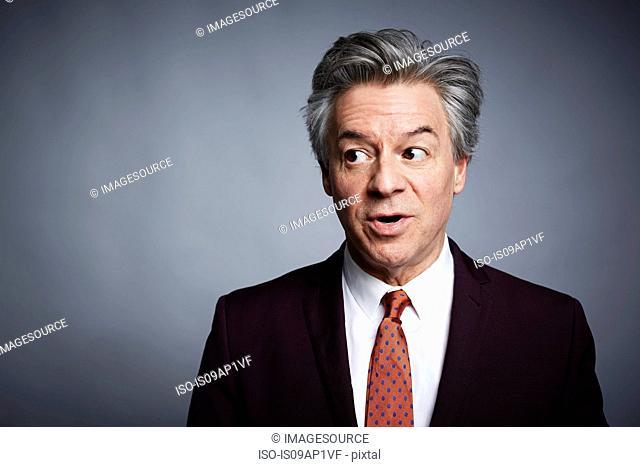 Studio portrait of mature businessman looking sideways