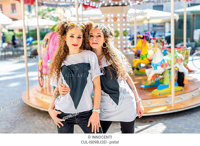 Fashion blogger twins in front of carousel, Mantova, Lombardia, Italy