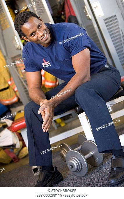 Fireman sitting on bench in fire station locker room