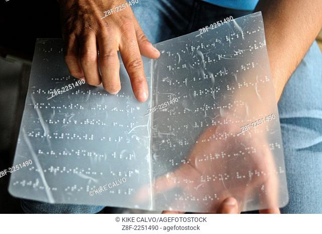 Blind man reading from a page written in braille