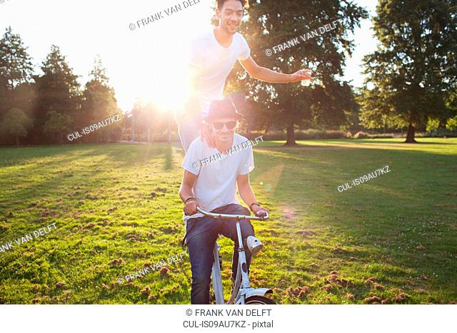 Party going man arriving in park standing on back of bicycle at sunset