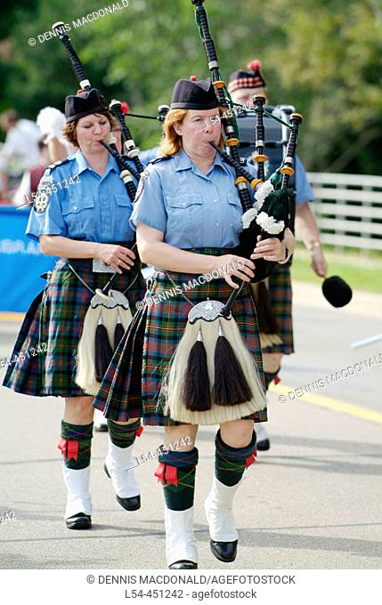 Portrait of Bag pipers playing music as they march in a parade