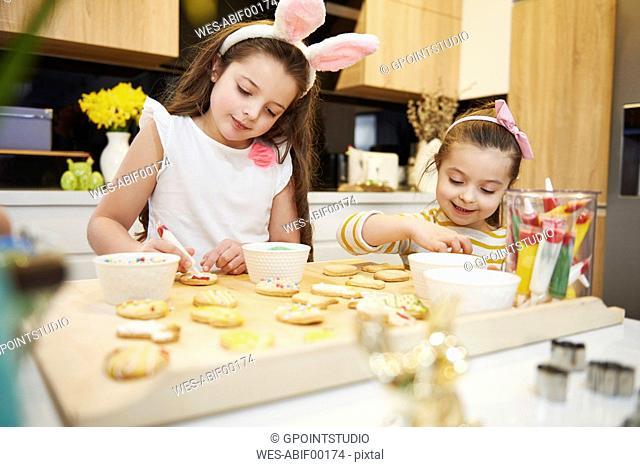 Sisters decorating Easter cookies in kitchen