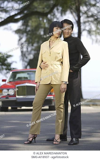 Well dressed couple standing side by side, looking at camera, car in the background