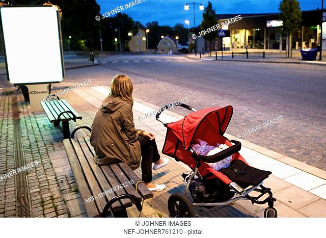 Woman waiting on a bench with a baby carriage, Sweden