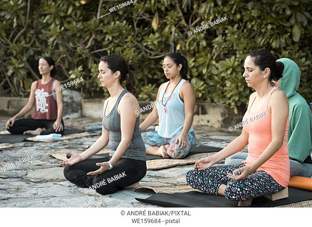 Group of five women meditating while sitting on yoga mats. Yoga retreat Puerto Vallarta - Mismaloya, Mexico