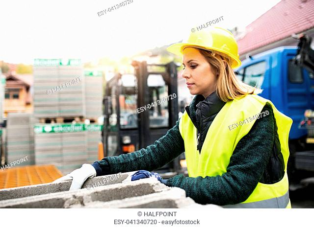 Female worker in an industrial area. Beautiful young woman working outside warehouse building