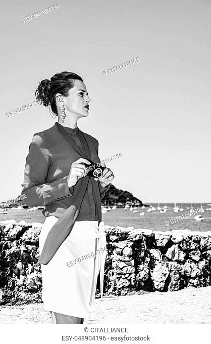 Luxury weekend retreat. modern woman in red blouse standing in front of the beautiful scenery overlooking lagoon with yachts in Donostia; San Sebastian