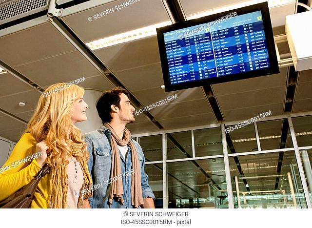 Couple checking flight times in airport