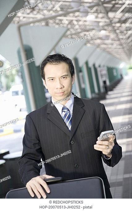 Portrait of a businessman using a palmtop and pushing a luggage cart