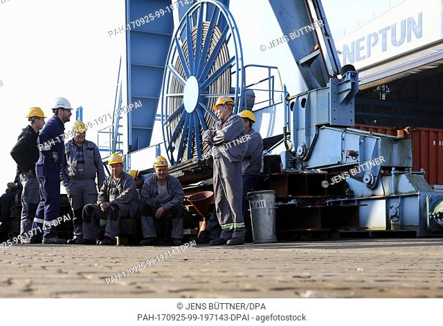 Dockworkers watch the first of two engine room modules for the cruise ship Aidanova being pulled out of the Neptun dockyard in Rostock, Germany