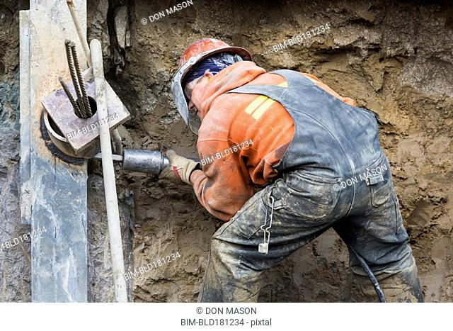 Caucasian worker drilling at construction site