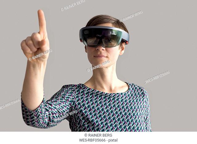 Woman wearing mixed reality smartglasses raising her hand