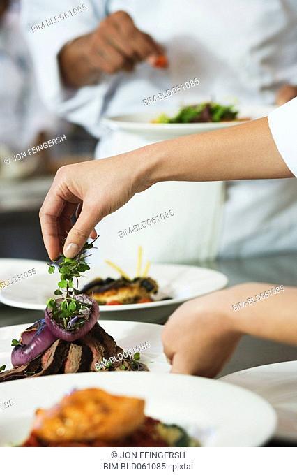 Chef putting garnish on plate of food
