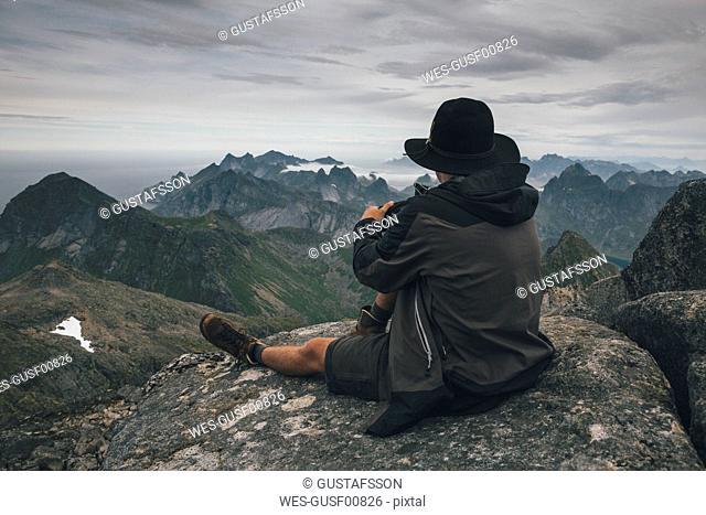 Norway, Lofoten, Moskenesoy, Young man sitting at Hermannsdalstinden, looking over Kjerkefjord