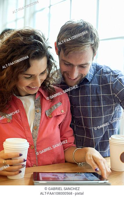 Couple using digital tablet in coffee shop