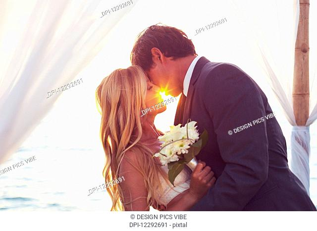 Beautiful Sunset Wedding by the Sea. Bride and Groom Kissing at Sunset. Romantic Married Couple