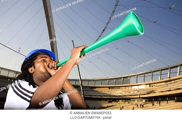 Construction worker wearing soccer outfit and blowing vuvuzela in front of Construction work, Moses Mabhida Stadium, Durban, KwaZului-Natal Province