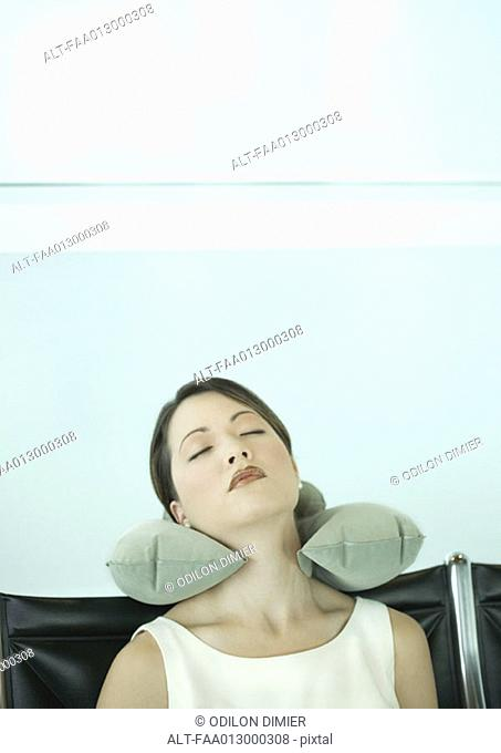 Young woman sleeping in airport lounge, using neck pillow