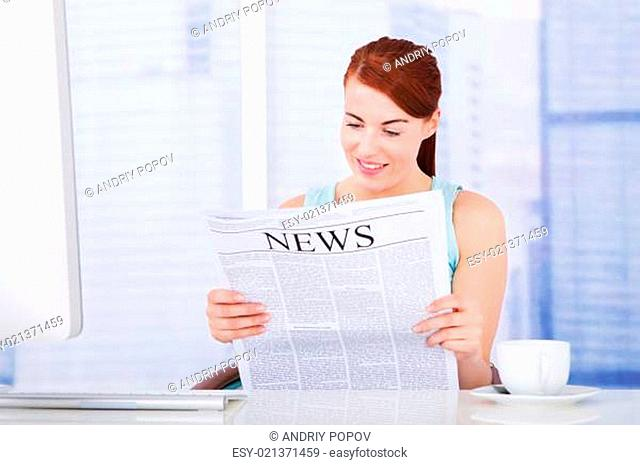 Woman Reading Newspaper At Computer Desk