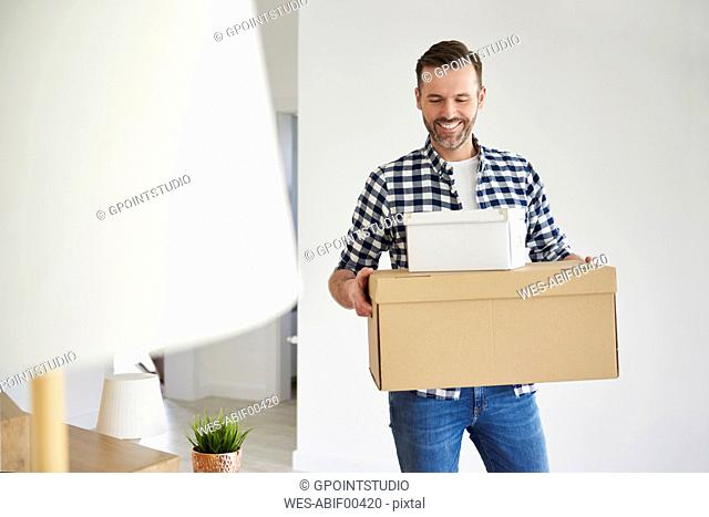 Happy man moving into new flat carrying cardboard box
