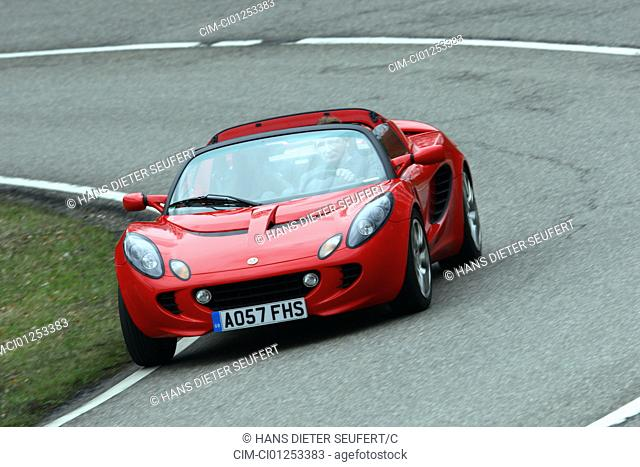 Lotus Elise SC, model year 2008-, red, driving, diagonal from the front, frontal view, country road, open top