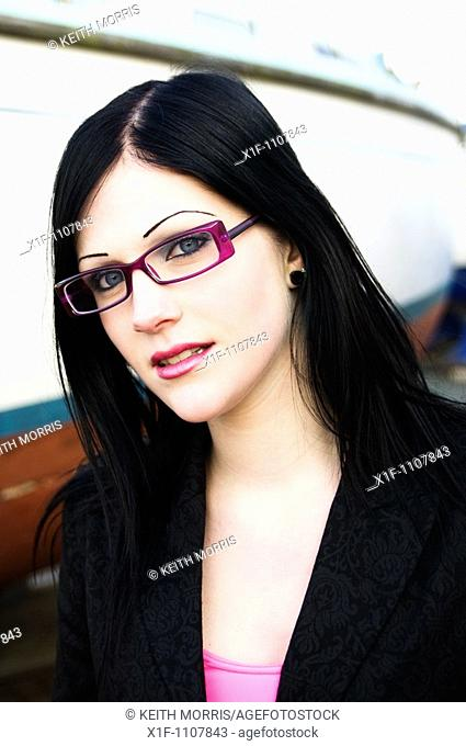 an attractive teenage girl with long black hair wearing glasses
