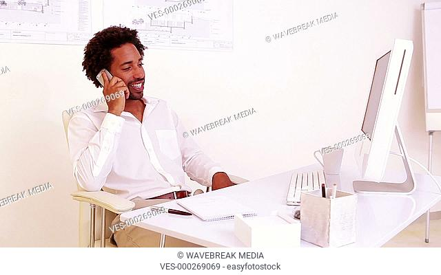 Businessman talking on phone at his desk