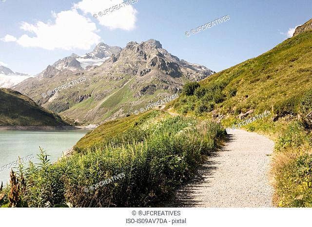 Pathway by water to mountain range, Partenen, Vorarlberg, Austria