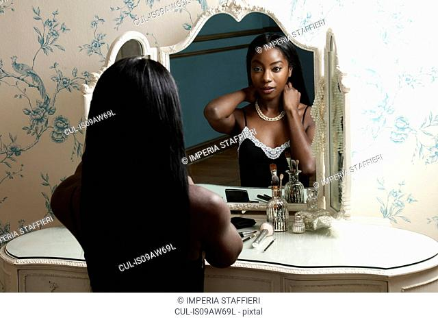 Young woman sitting at dressing table, putting on necklace